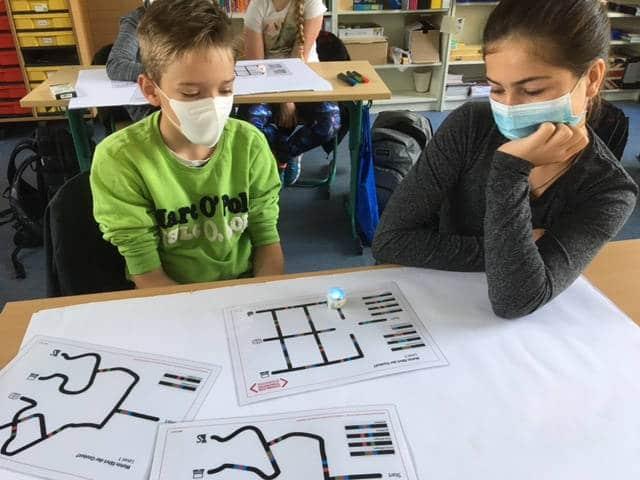 Aufgaben in verschiedenen Schwierigkeitsstufen erfordern die Programmierung des Ozobot mittels der Farbcodierungen, damit er eine gestellte Aufgabe löst.