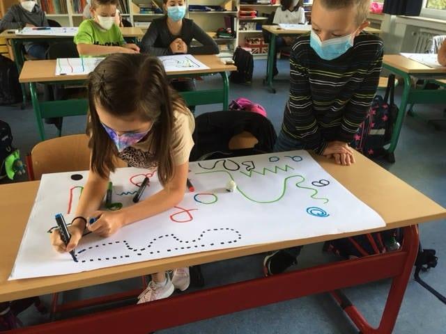 Ozobot, die weiße Kugel auf dem Papier, fährt automatisch farbige Strecken ab, die die Kinder frei zeichnen. Die Farben haben dabei zusätzliche steuernde Bedeutung für den Ozobot.